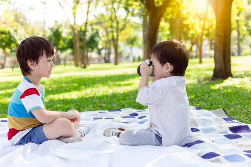 Handsome younger brother or little boy taking photo for his older brother by using camera at park in summer season. They're. Brotherhood and love each royalty free stock images