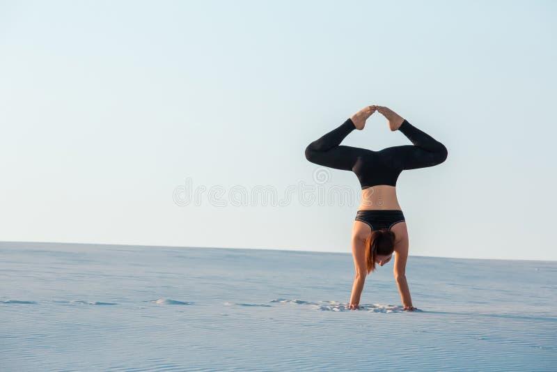 Handstand представления йоги заворота молодой женщины практикуя балансируя на песке стоковые фотографии rf