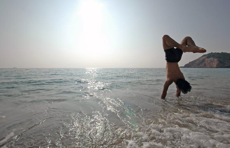 Handstand auf dem Strand #2 lizenzfreies stockfoto