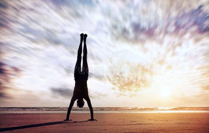 Handstand dichtbij de oceaan stock foto