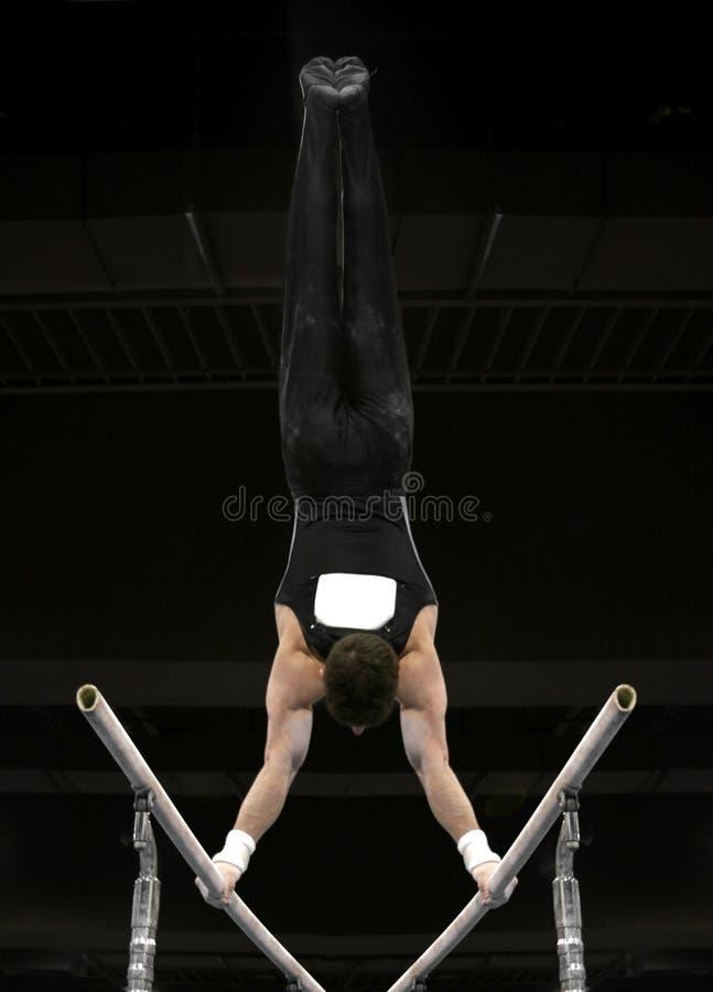 Handstand en barrases paralelas imagen de archivo