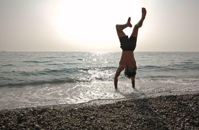 Handstand sulla spiaggia fotografie stock libere da diritti