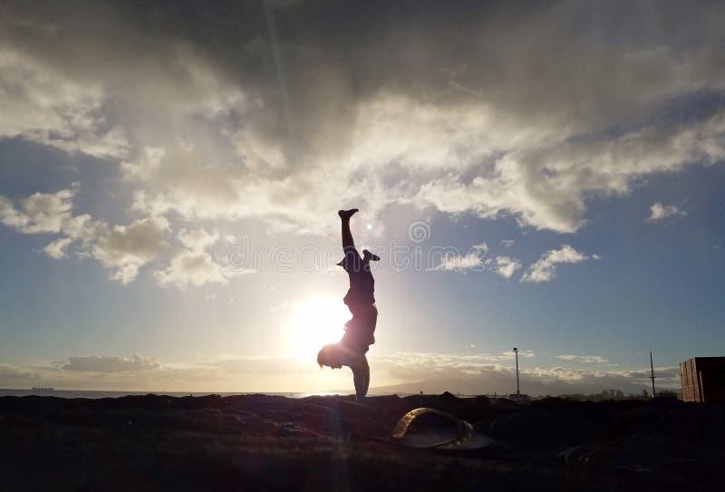 Handstand van het mensen de gespleten been op kustrotsen bij zonsondergang royalty-vrije stock foto's