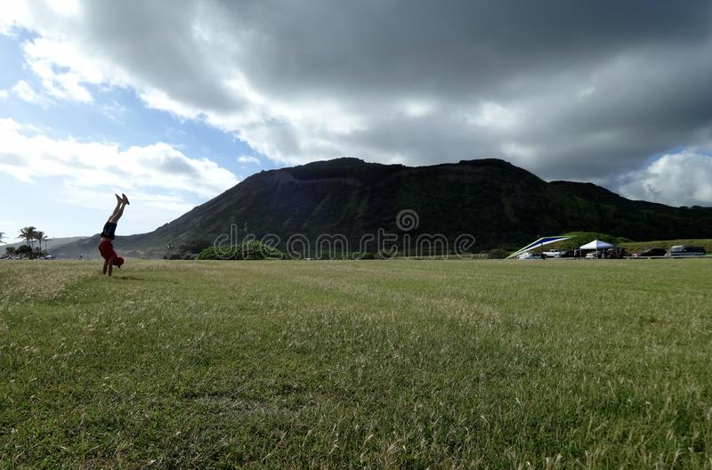 Handstanding at Sandy Beach Park with Koko Head Crater in the background. Man wearing hat, shirt, shorts, and slippers Handstanding at Sandy Beach Park with Koko royalty free stock image