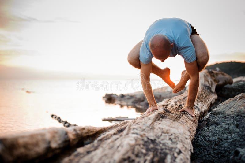 Handstansyoga poserar vid mannen på stranden nära havet royaltyfria foton