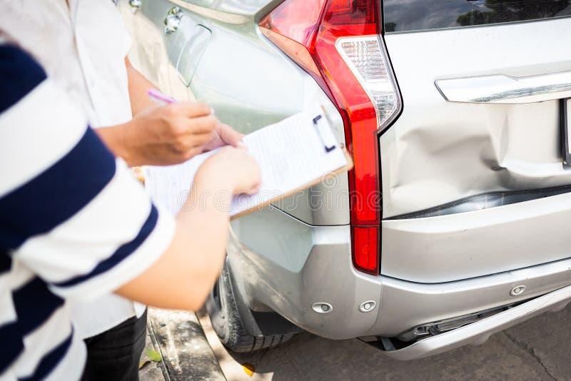 Handstil för försäkringmedel på skrivplattan, medan undersöka bilen aft arkivbild