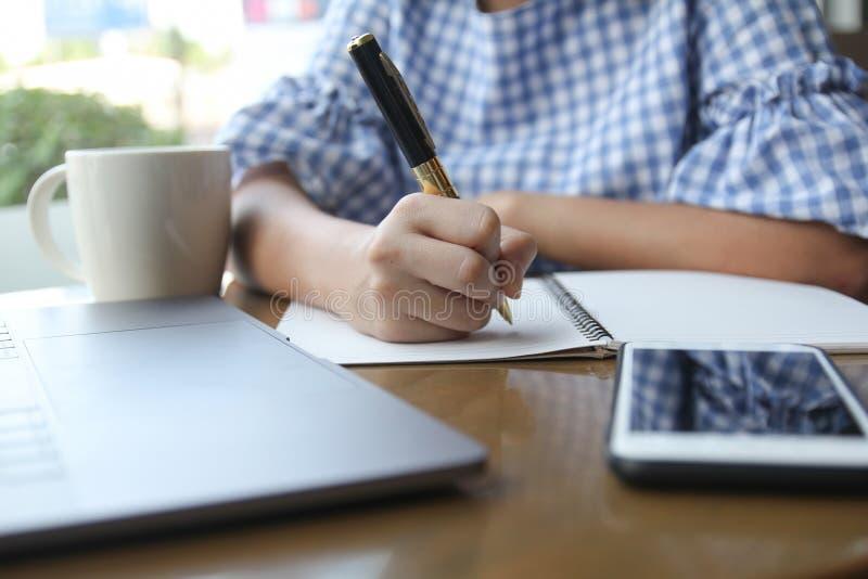Handstil för penna för innehav för affärskvinna på den vita tomma anteckningsboken på wo arkivfoton