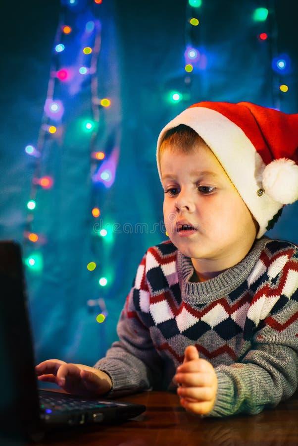 Handstilbokstav för litet barn till Santa Claus på bärbar datordatoren Pys med jultomtenhatten arkivbild