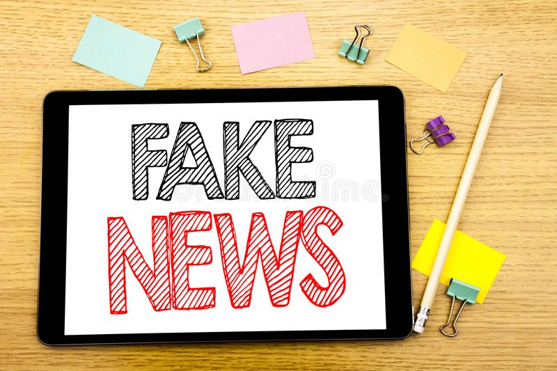 Handstiltextvisningen fejkar nyheterna Affärsidé för Hoax journalistik som är skriftlig på minnestavlabärbara datorn, träbakgrund arkivfoto