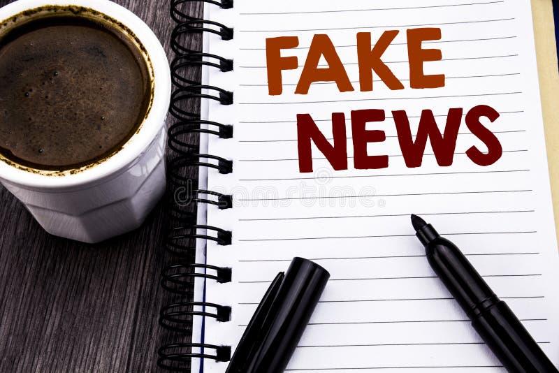 Handstiltextvisningen fejkar nyheterna Affärsidé för Hoax journalistik som är skriftlig på papper för anteckningsbokbokanmärkning arkivbilder