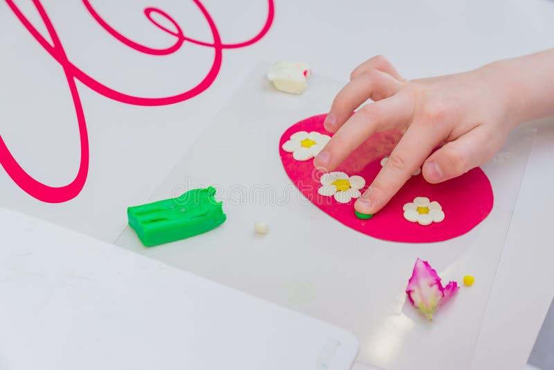 Handtag av små flickor som tillverkar vårkort med blommor från färgad lerdeg av plast royaltyfri fotografi
