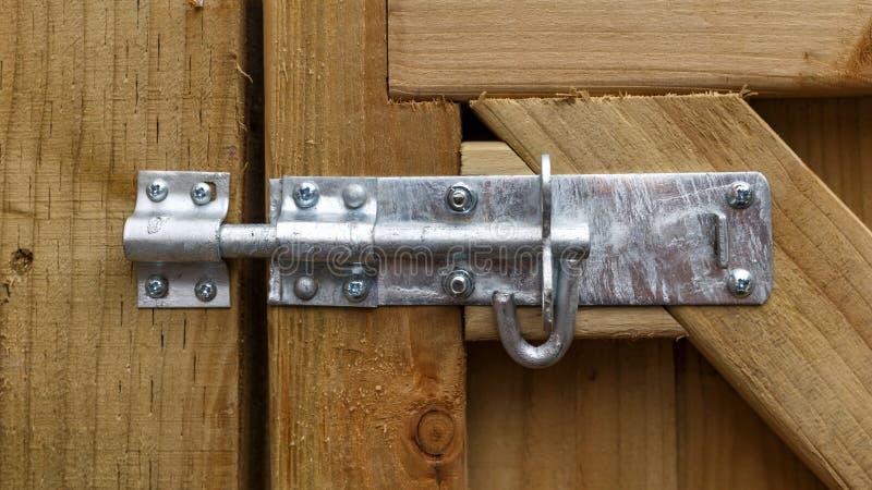 Handtag för glidlås av metall, monterad på träträdgårdsgrind, dörrbult arkivbild
