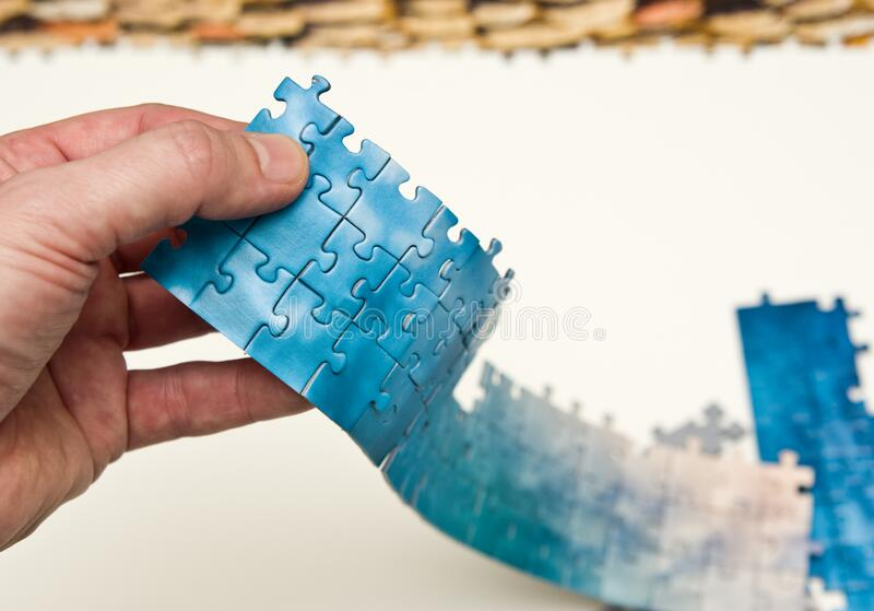 Handtag med en rand av blå pussel arkivbilder