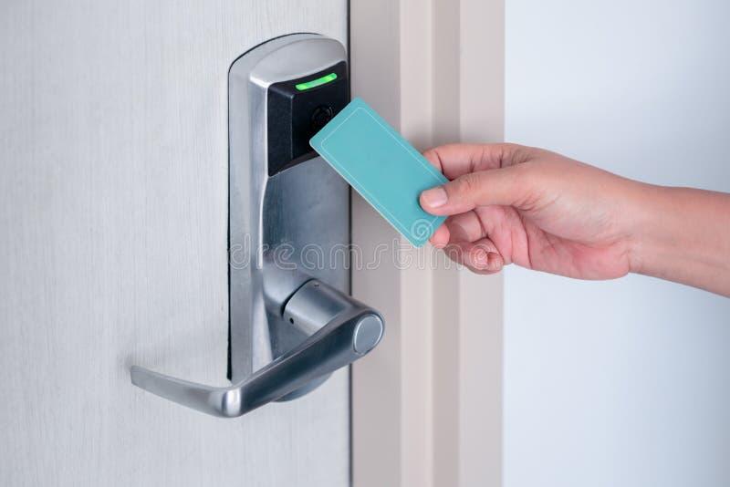 Handtag med hjälp av ett elektroniskt, kontaktlöst nyckelkort för att låsa upp dörren på hotell eller i hus royaltyfria bilder
