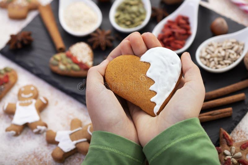 Handtag som håller gingerbröd med vitt frostande - kärlekschristmas matkoncept royaltyfri foto
