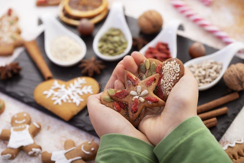 Handtag som håller kakor av kryddbröd som dekorerats med naturliga frön och torkade bär - semestergodis royaltyfri fotografi