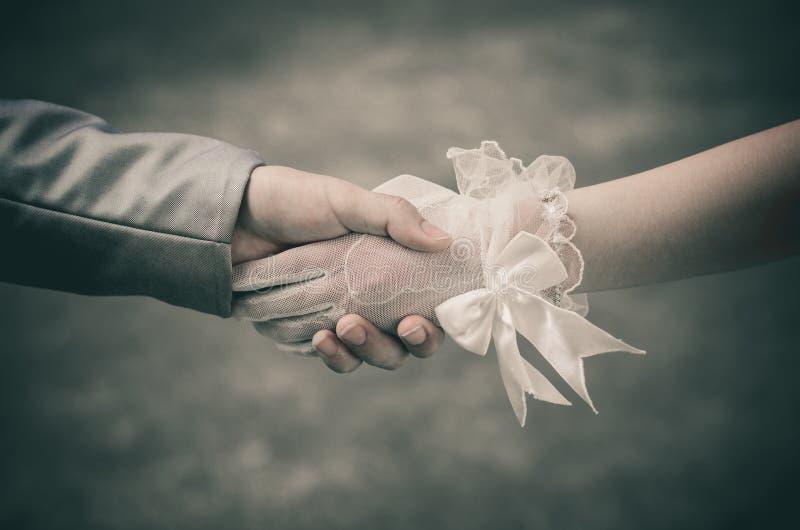 Handtaget visar att förälskelsen mellan bruden och brudgummen ska gå bort med en överenskommelse och för evigt fotografering för bildbyråer
