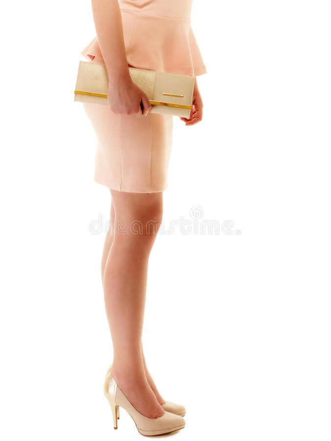 Handtas en benen van meisje in roze kleding en hoge hielen stock foto's