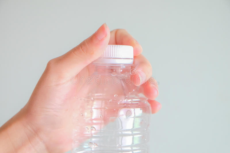 Handtorsionsflasche mit grauem Hintergrund stockbild