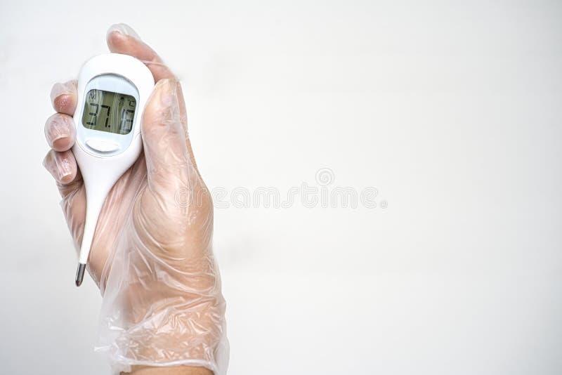 Handtragender Sanitärhandschuh mit digitalem Thermometer Celsius-Skala auf weißem Hintergrund Leerzeichen kopieren stockfoto