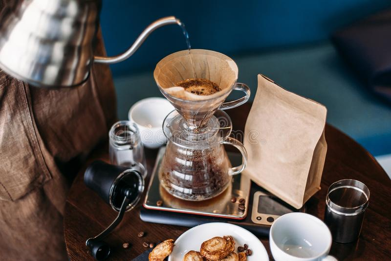 Handtropfenfänger-Kaffeeausrüstung, barista strömendes Wasser auf Kaffeesatzesprit lizenzfreie stockfotografie