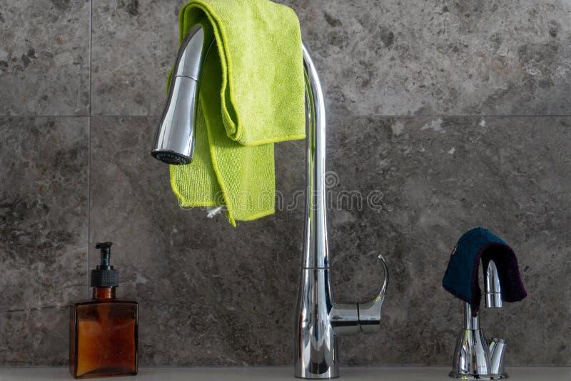 Handtvålpump, kromdiskhovattenkran, filtrerat vattenklapp med microfibretorkdukar och grå backsplash för marmorstentegelplatta arkivbilder