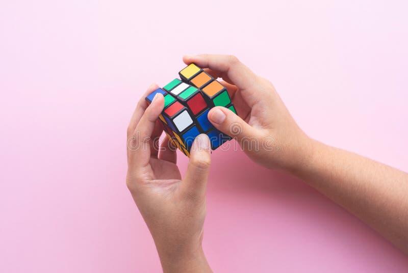 Handunge som spelar den färgrika kuben lära med lösningsbegrepp Kreativitetutveckling royaltyfri fotografi