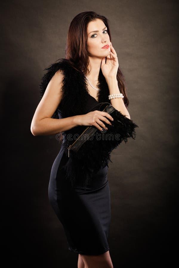 Handväska för kvinnaaftonklänning i hand på svart royaltyfri bild
