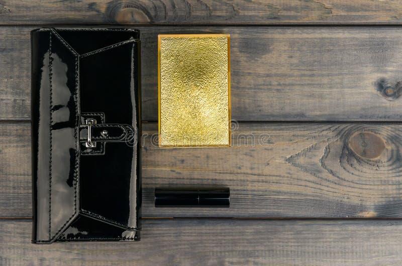 Handväska-koppling svart, pulverask med spegeln och läppstift guld- l fotografering för bildbyråer