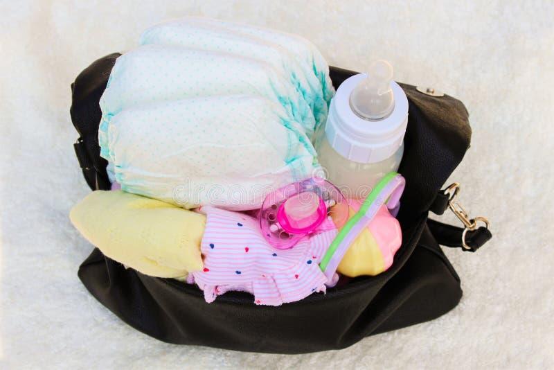 Handväska med objekt som att bry sig för barn arkivfoto