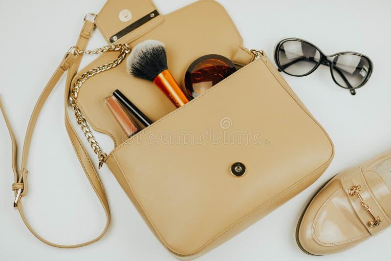 Handväska med skönhetsmedel solglasögon sko Vit bakgrund royaltyfri fotografi