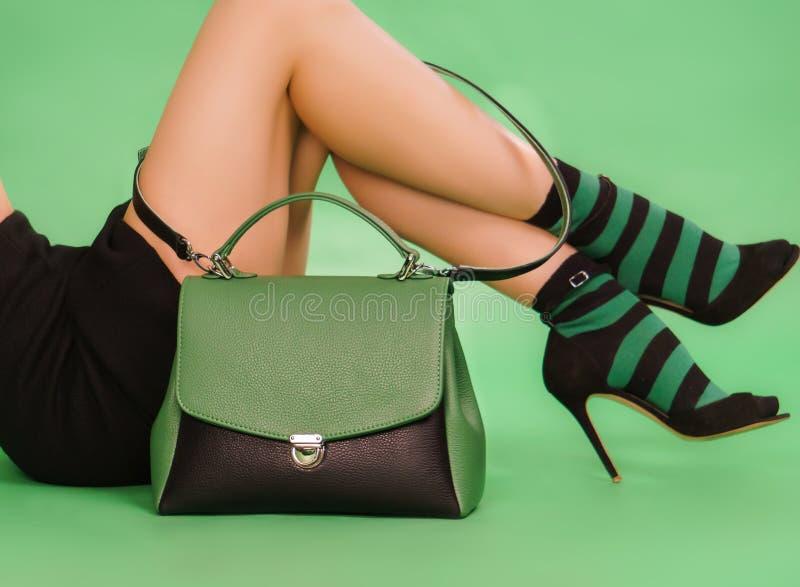 Handväska och ben för kvinna` s i gröna färger för en svartnad arkivbild