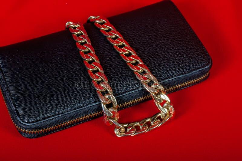 Handväska och en halsband på röd bakgrund royaltyfri bild