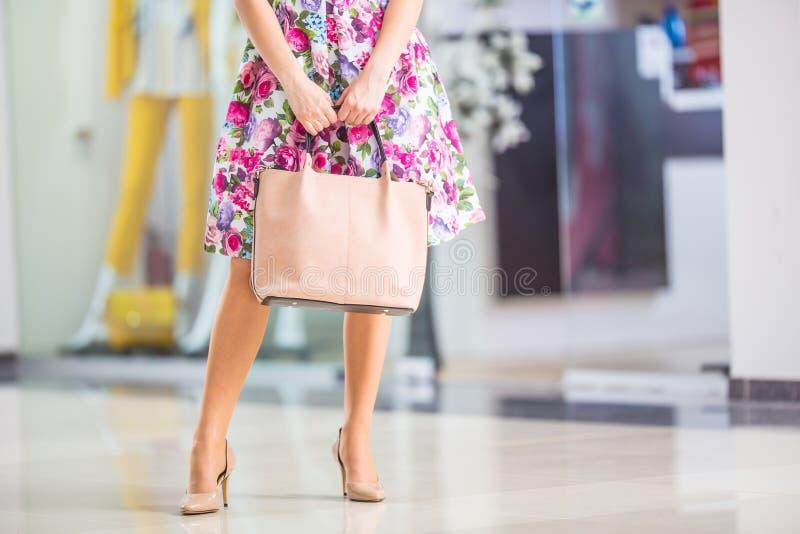 Handväska och skor för dräkt för sommar för ben för närbildkvinna sexig Stilfull tillfällig kvinna i shoppinggalleria royaltyfri fotografi