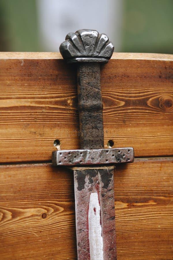 Handvat en deel van het zwaardblad, van de schede, close-up tegen een vage houten muur half wordt een ontslagen die royalty-vrije stock afbeelding