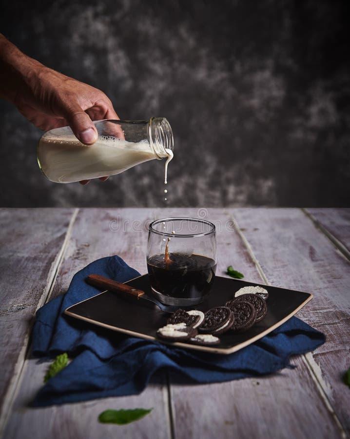Handvat melkfles die op glas koffie stroomt royalty-vrije stock fotografie