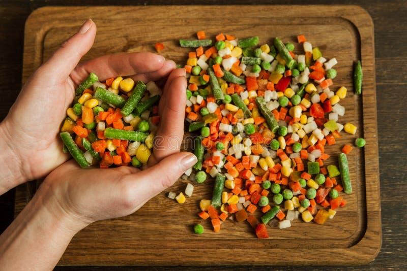 Handvol bevroren groenten op scherpe raad stock afbeeldingen