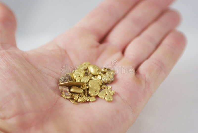 Handvoll Goldnuggets stockbilder
