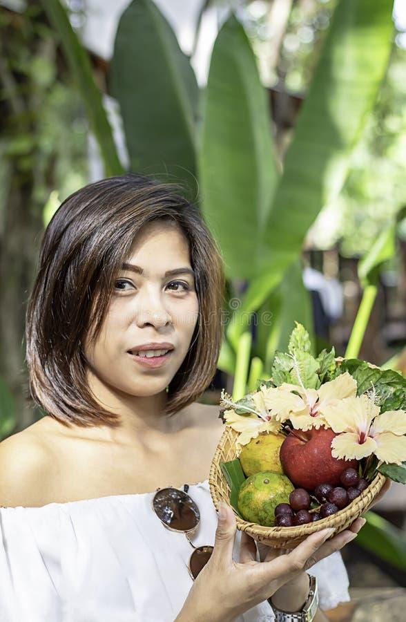 Handvrouw die de manden van het weefselbamboe met van Apple, van de Sinaasappel en van de druif onscherpe bomen Als achtergrond h stock afbeeldingen