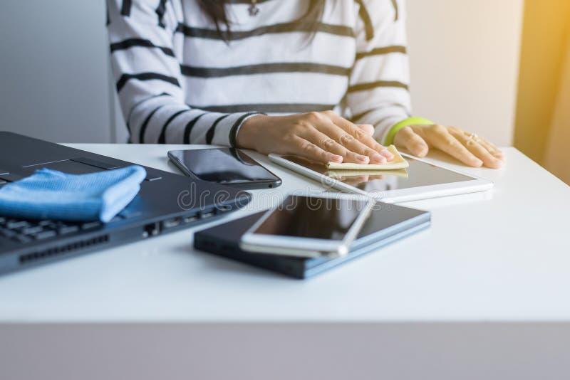 Handvrouw die haar tablet op het scherm met microfiberdoek schoonmaken stock afbeelding