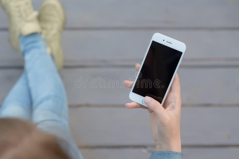 Handvrouw die smartphone buiten hout gebruikt stock afbeeldingen