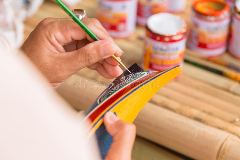 Handwerk, das hölzernes Miniaturboot malt stockfoto