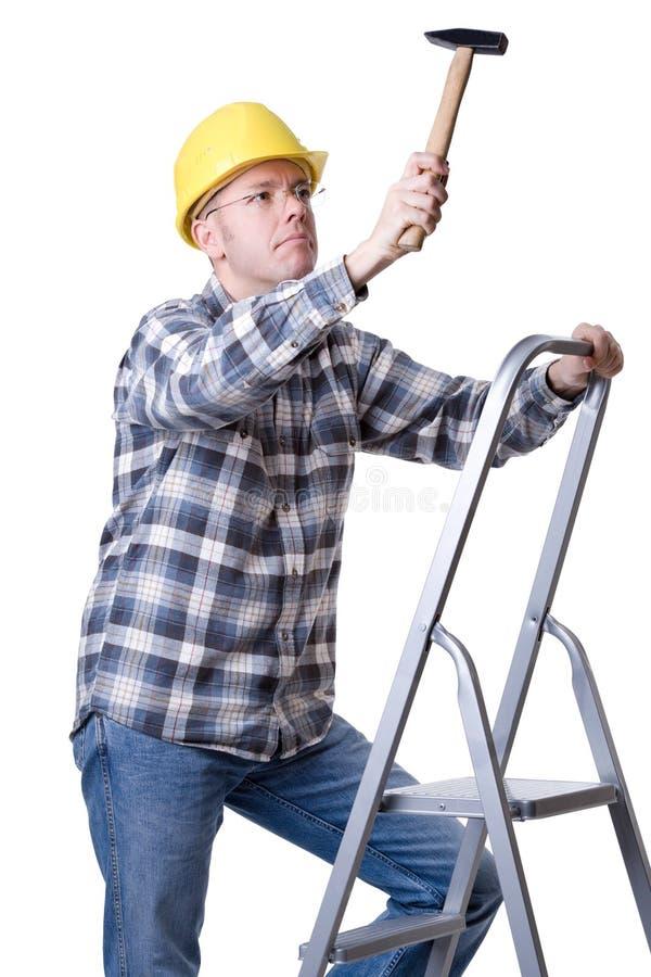 Handwerker auf einer Strichleiter mit einem Hammer stockbilder