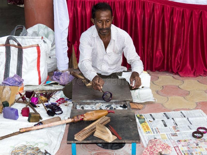 Handwerker, der traditionelle Gummilackarmbänder herstellt lizenzfreie stockbilder