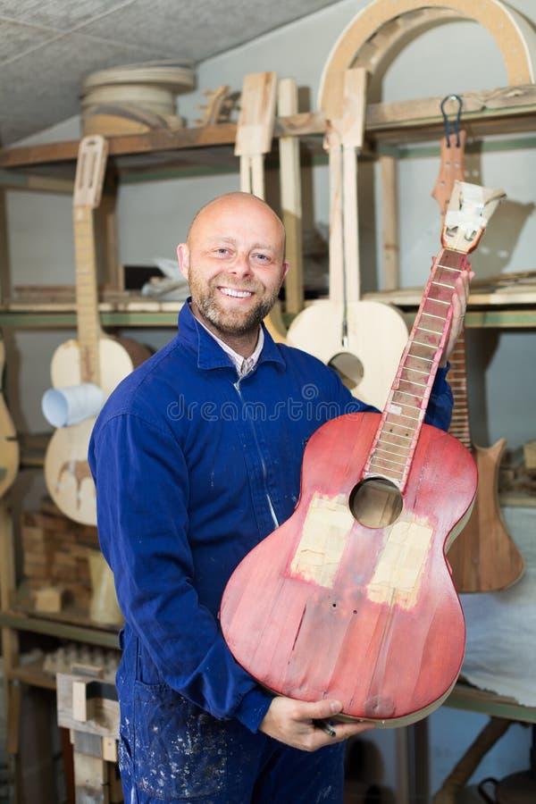 Handwerker, der unfertige Gitarre hält lizenzfreies stockbild