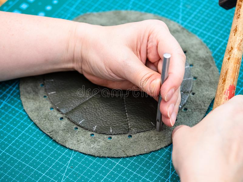 Handwerker macht Perforierung im genähten Beutel lizenzfreies stockbild