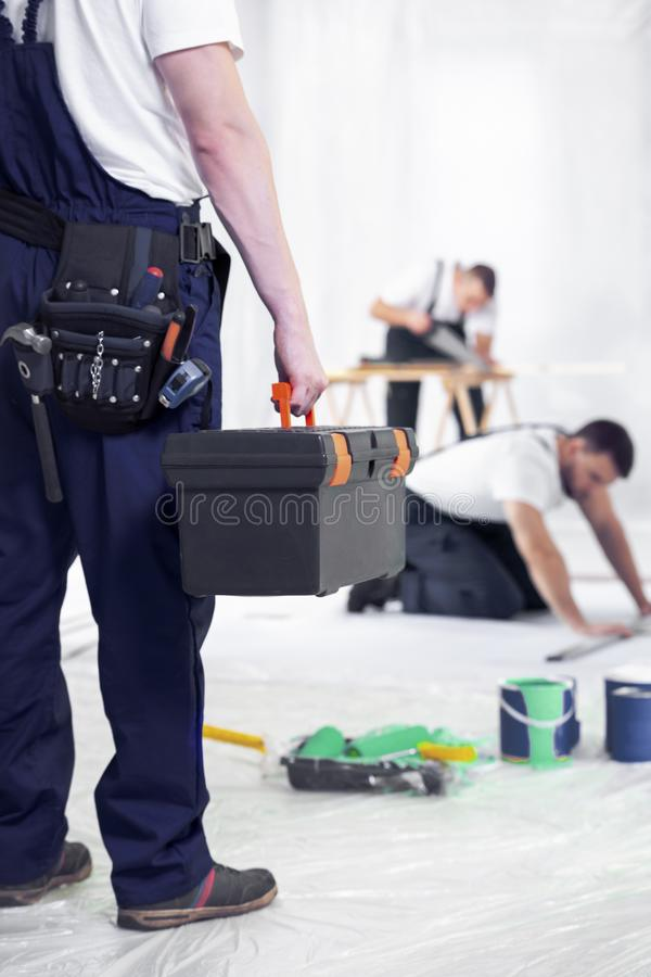 Handwerker mit Werkzeugkasten während der Arbeit der Haupterneuerungsmannschaft lizenzfreie stockbilder