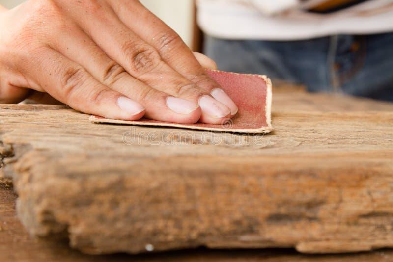 Handwerker Run das Sandpapier über der Holzoberfläche stockfotos