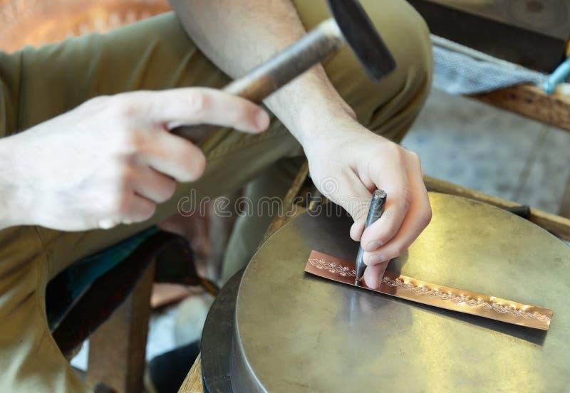 Handwerker stellt kupfernes Armband her stockfotos
