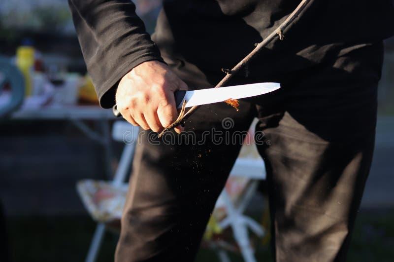 Handwerker versucht hölzernes Stockschleifen weg zu ährentragendem Stock Bereites Werkzeug für das Grillen Grill wurde begonnen W stockbild